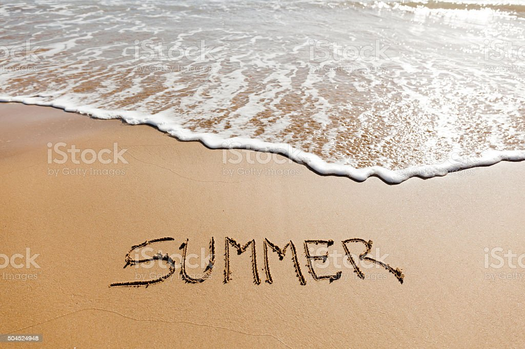 Summer written in the sand on a beach. stock photo
