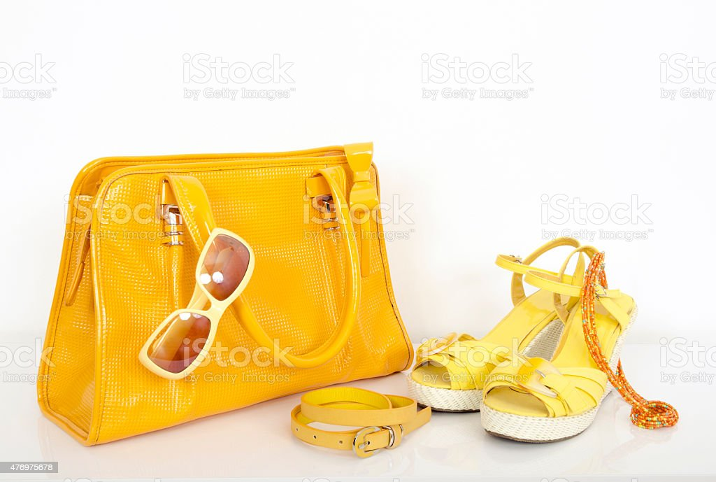 Summer yellow purse with matching sandals and accessories. stock photo