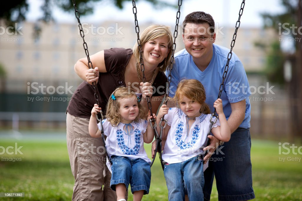 summer young family park swings royalty-free stock photo