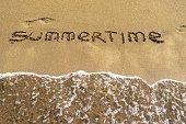 summertime an inscription on wet sand closeup