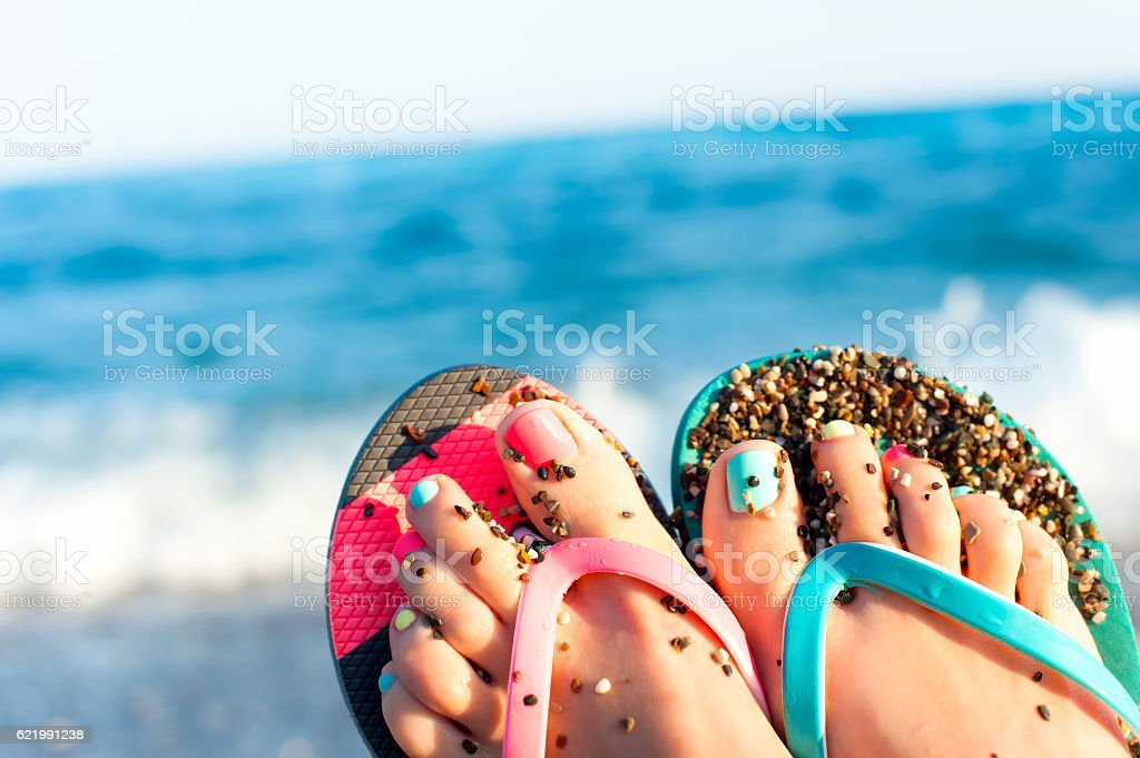 Summertime enjoyment! Lady's feet on the beach. Ocean waves background. stock photo