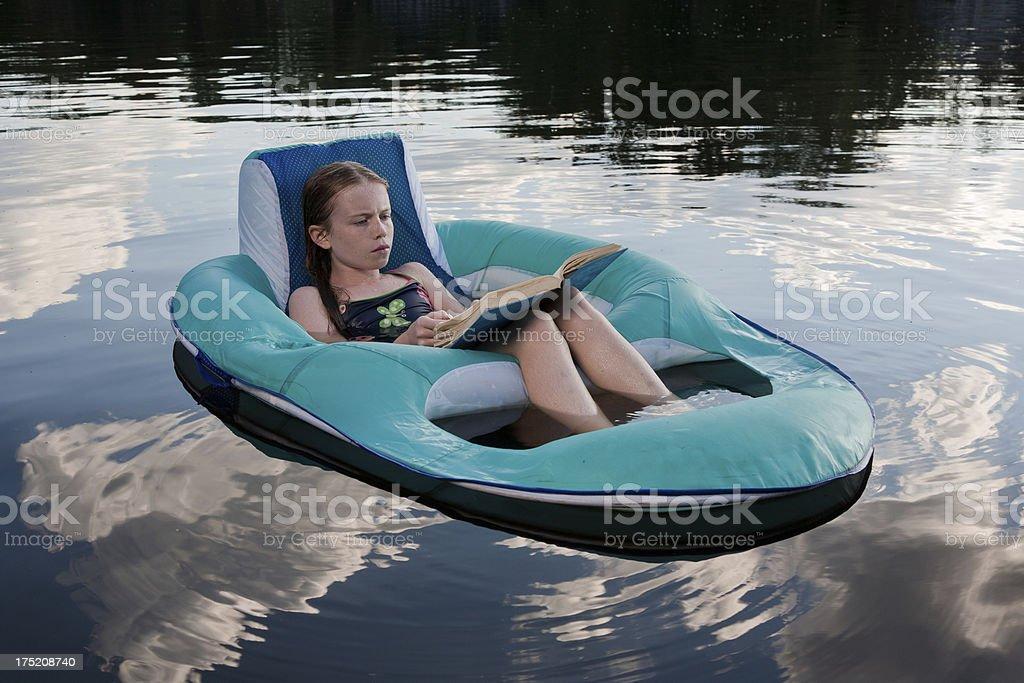 Summertime reading at a lake royalty-free stock photo