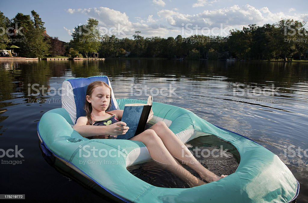 Summertime reading at a lake royalty-free stock photo