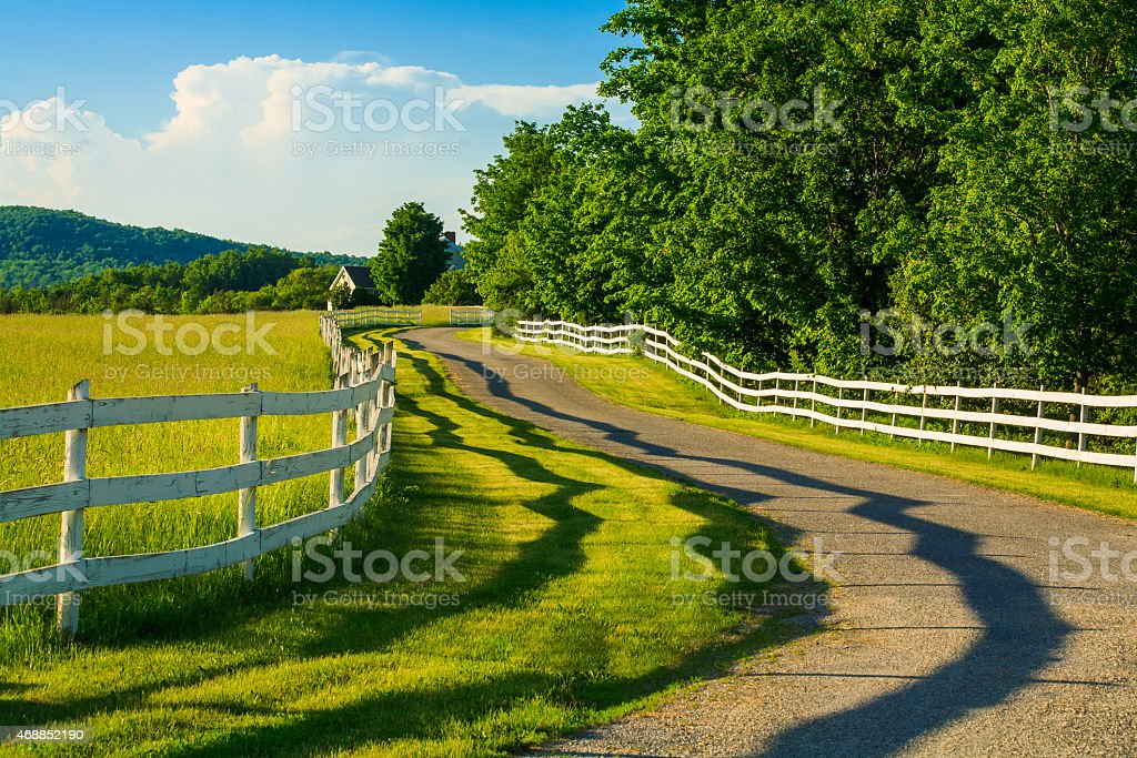summertime winding country road, white rail fence, hay, shadows, vermont stock photo
