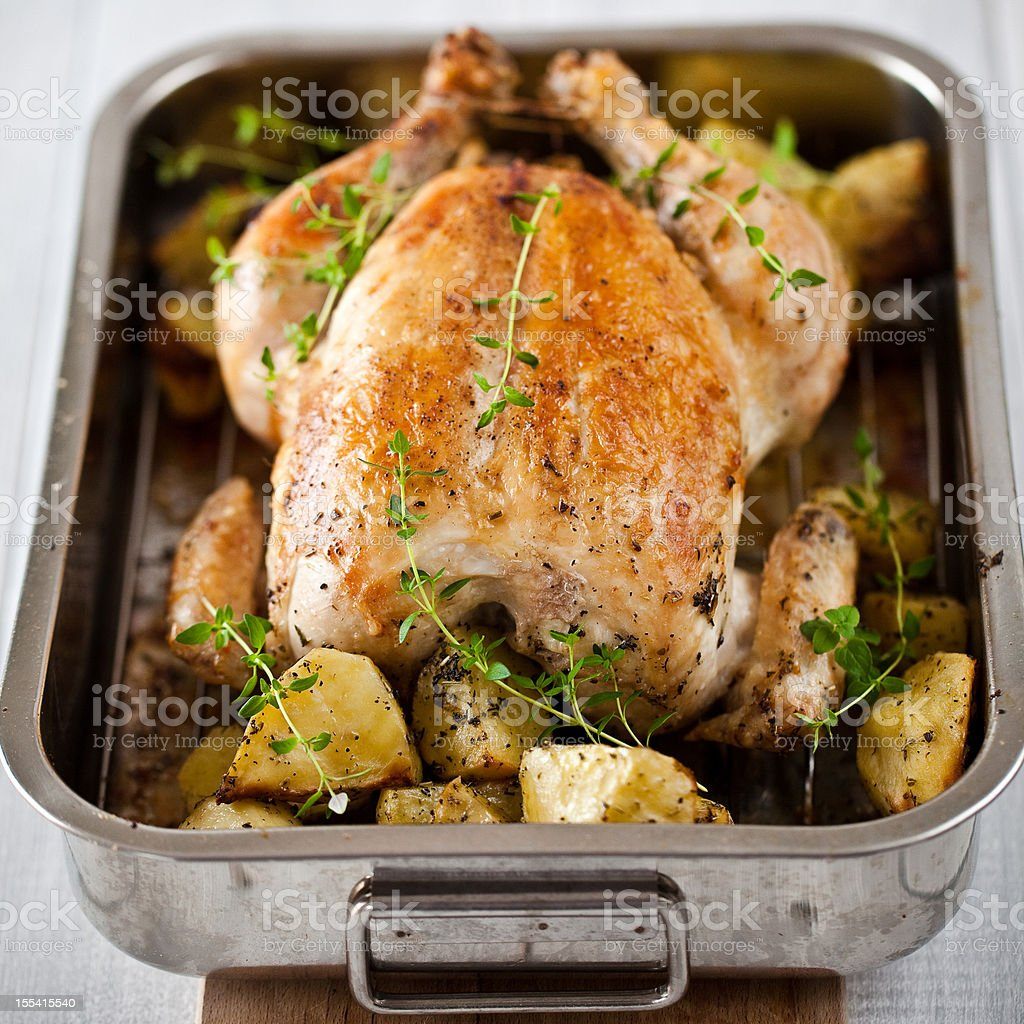 Sumptuous roasted chicken with herbs and potatoes  stock photo