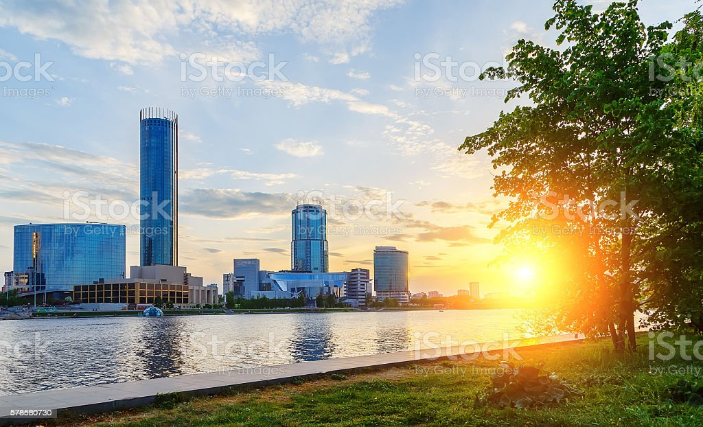 sun and beautiful sunset over city center and pond stock photo