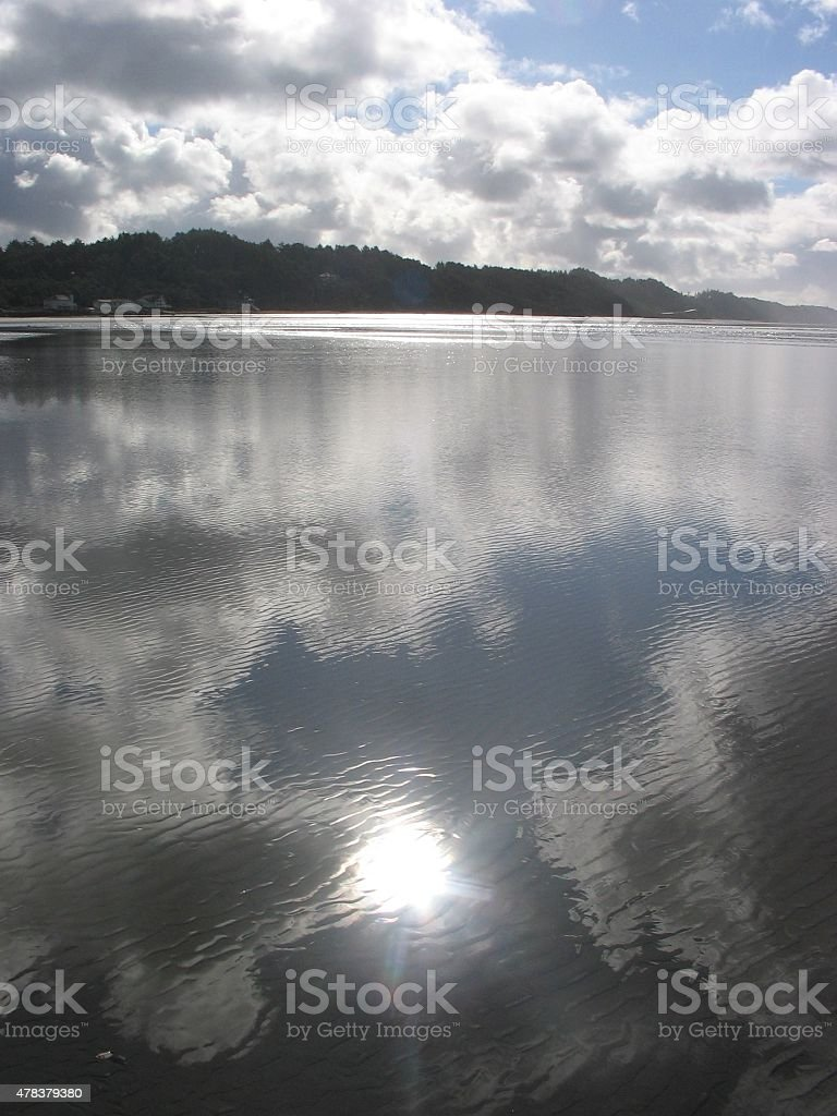 Sun and Clouds Reflectng on Sand stock photo