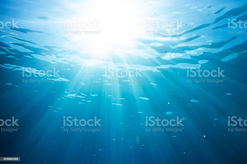 sun and sunbeams in the ocean water stock photo