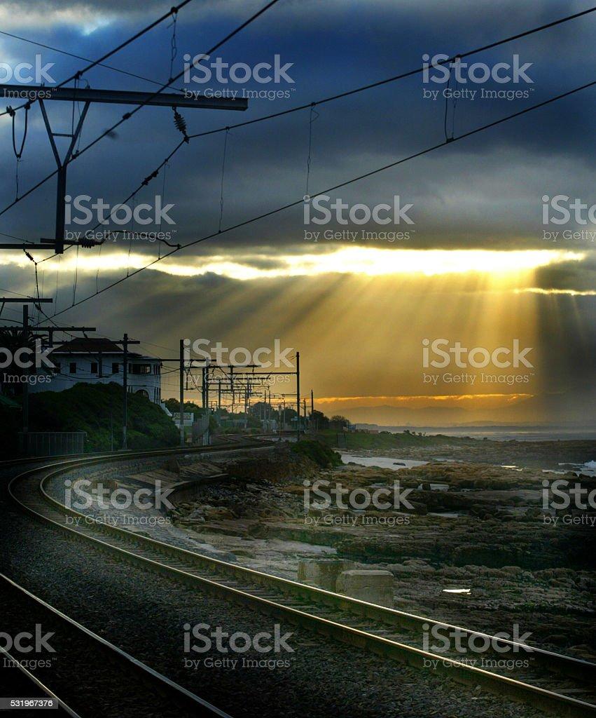 Sun beams over railway at sunset stock photo