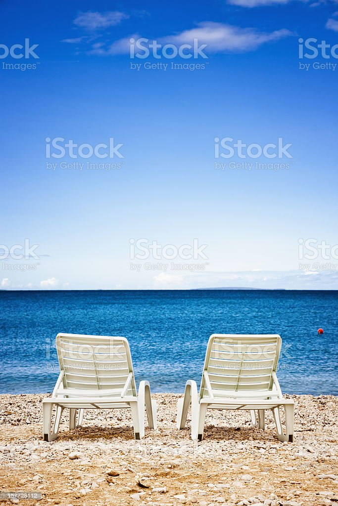 Sun beds at lonely beach royalty-free stock photo