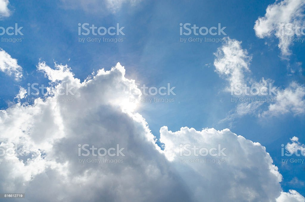 Sun behind cloud and blue sky stock photo