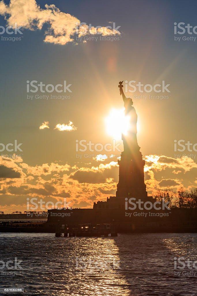 Sun behind statue of liberty. stock photo
