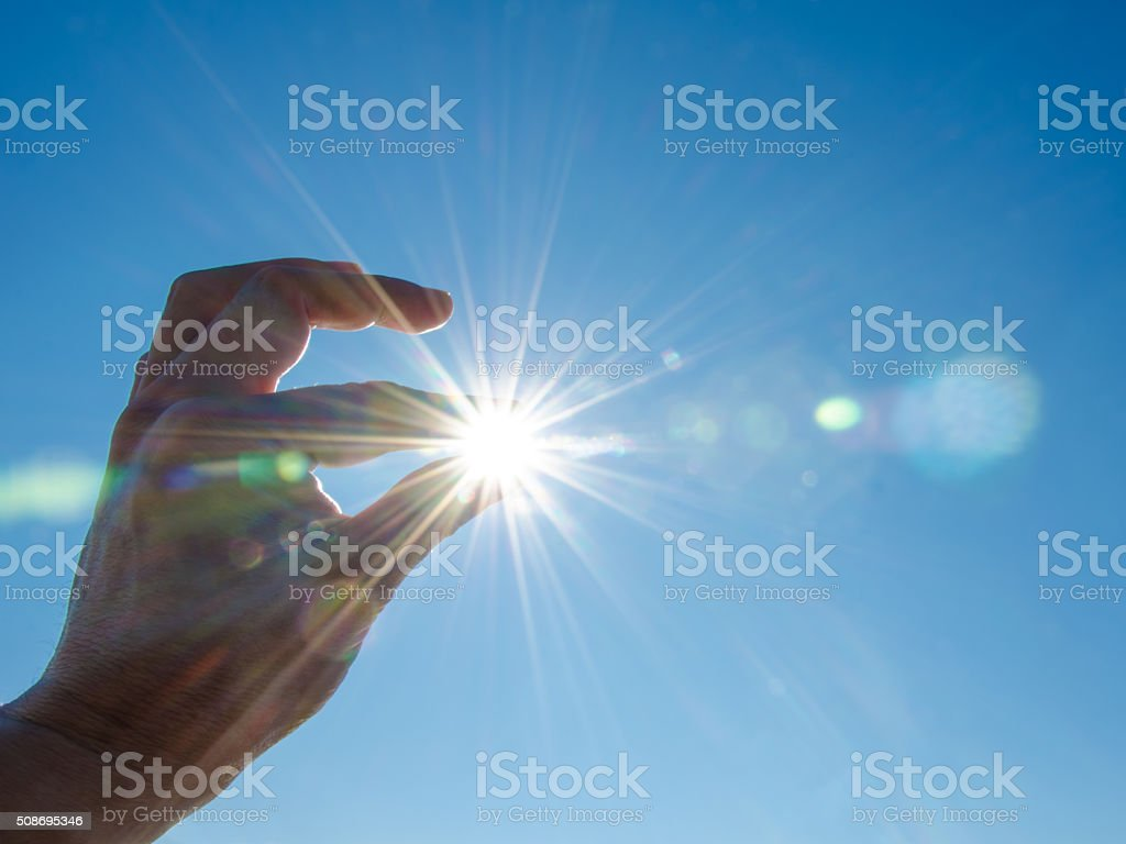 Sun between fingers stock photo