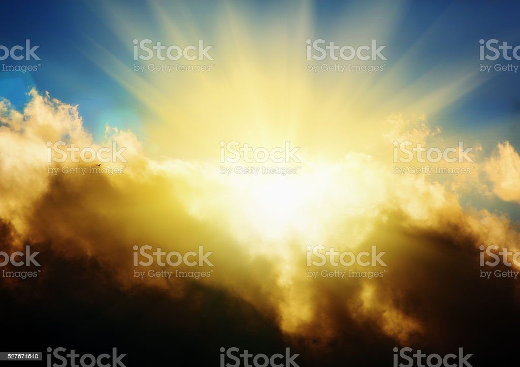 Sun breaking through clouds as tiny, silhouetted bird flies by stock photo