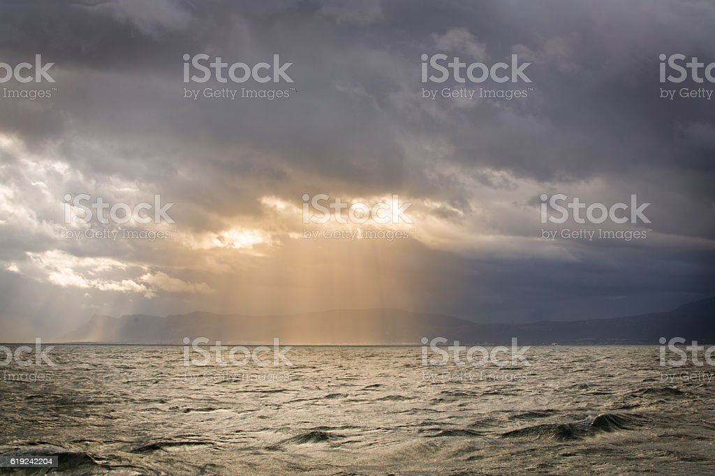 Sun breaking through Clouds stock photo