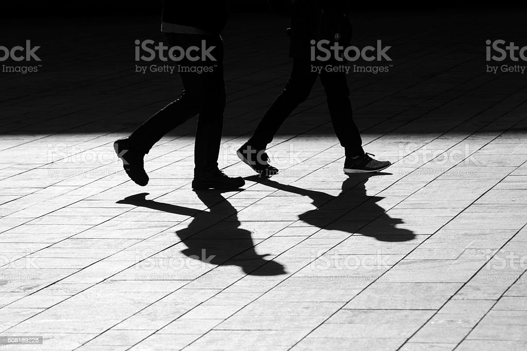 sun casting shadow over two people walking on the street stock photo