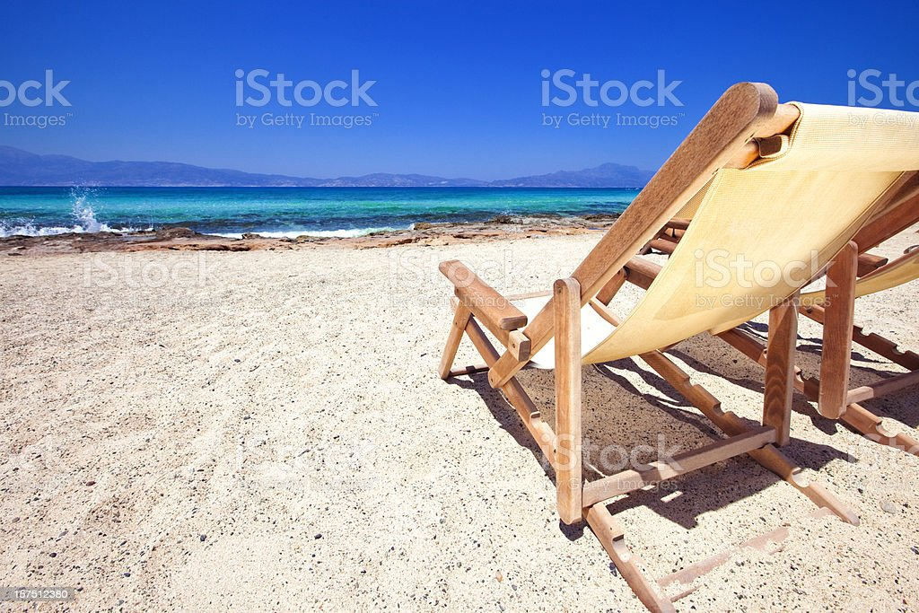 Sun chairs on sandy beach royalty-free stock photo