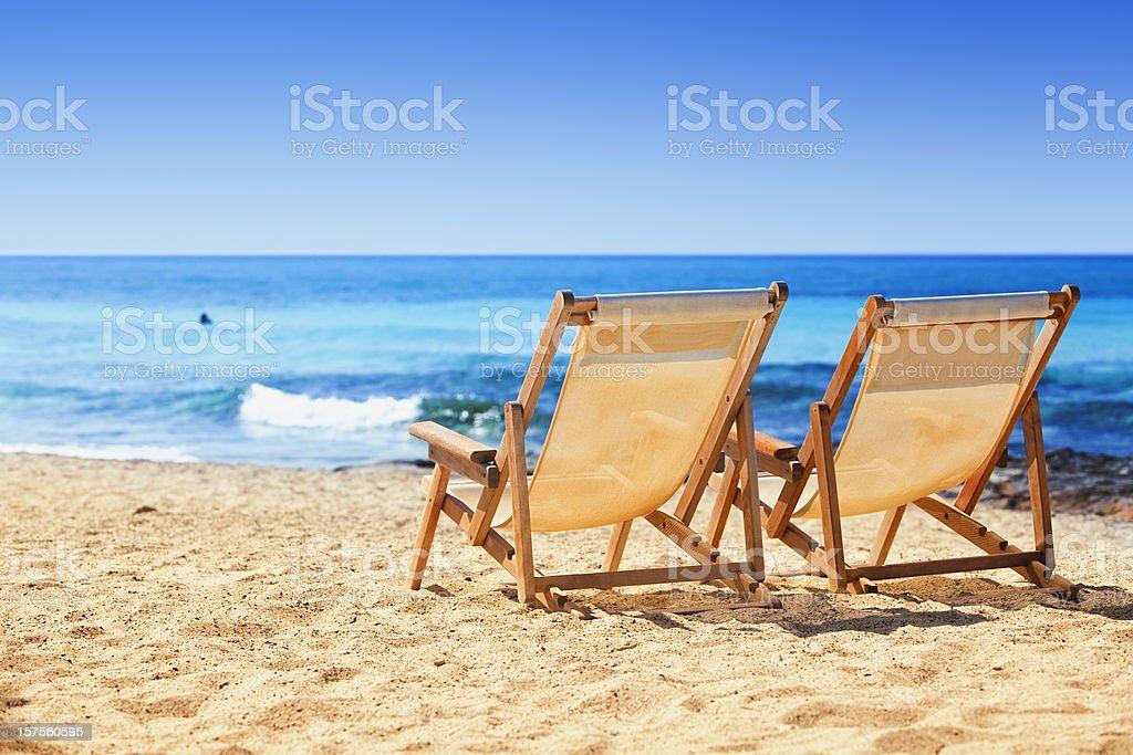 Sun chairs on sandy beach royalty-free stock photo