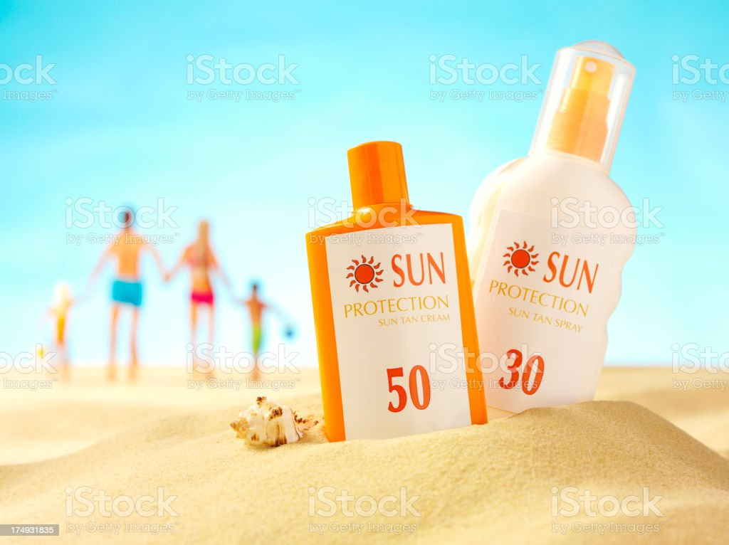 Sun Cream in the Sand with a Family Holding Hands stock photo