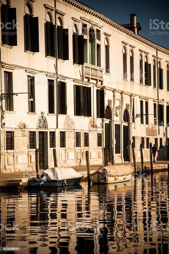 Sun Drenched Venice Canal with Moored Boats stock photo