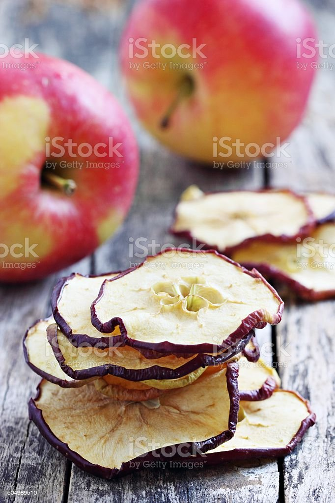 Sun dried apple chips on a rustic wooden table.Healthy snack stock photo