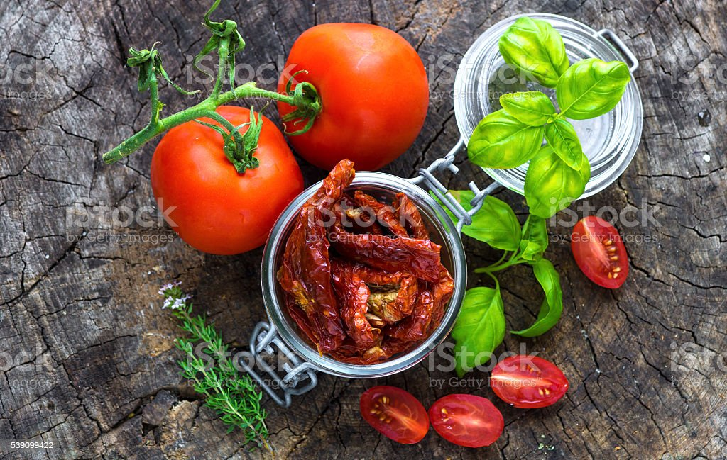 Sun dried tomatoes on wooden background stock photo