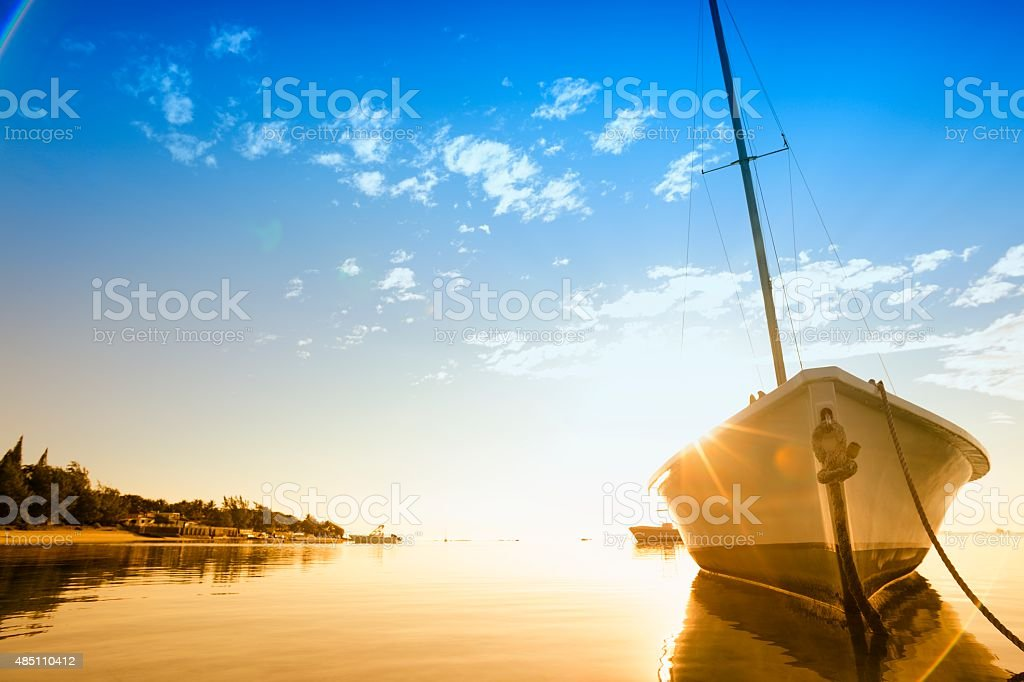 Sun flare around sailboat hull on a tropical beach stock photo