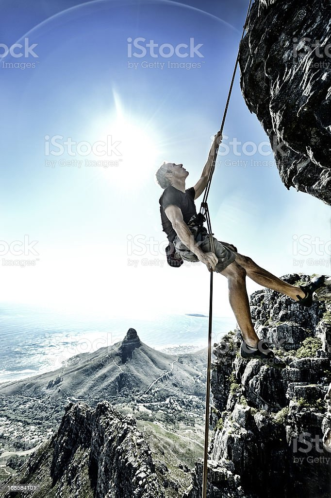Sun flares surround abseiling climber on Table Mountain stock photo