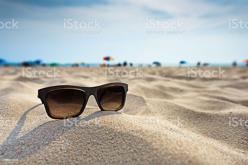 Sun glasses lie on a beach near the sea. stock photo
