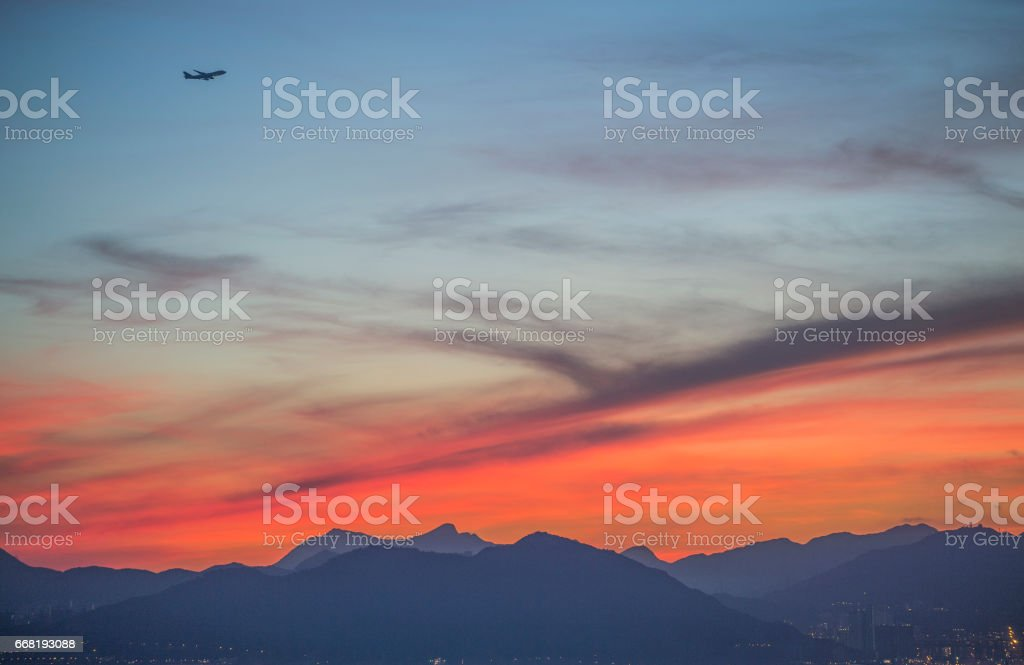 Sun glow with aeroplane over West Kowloon, Hong Kong, at dawn stock photo