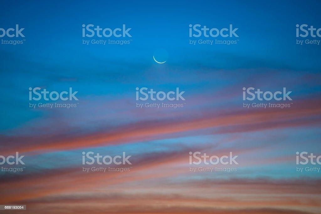 Sun glow with moon in Hong Kong at dawn stock photo