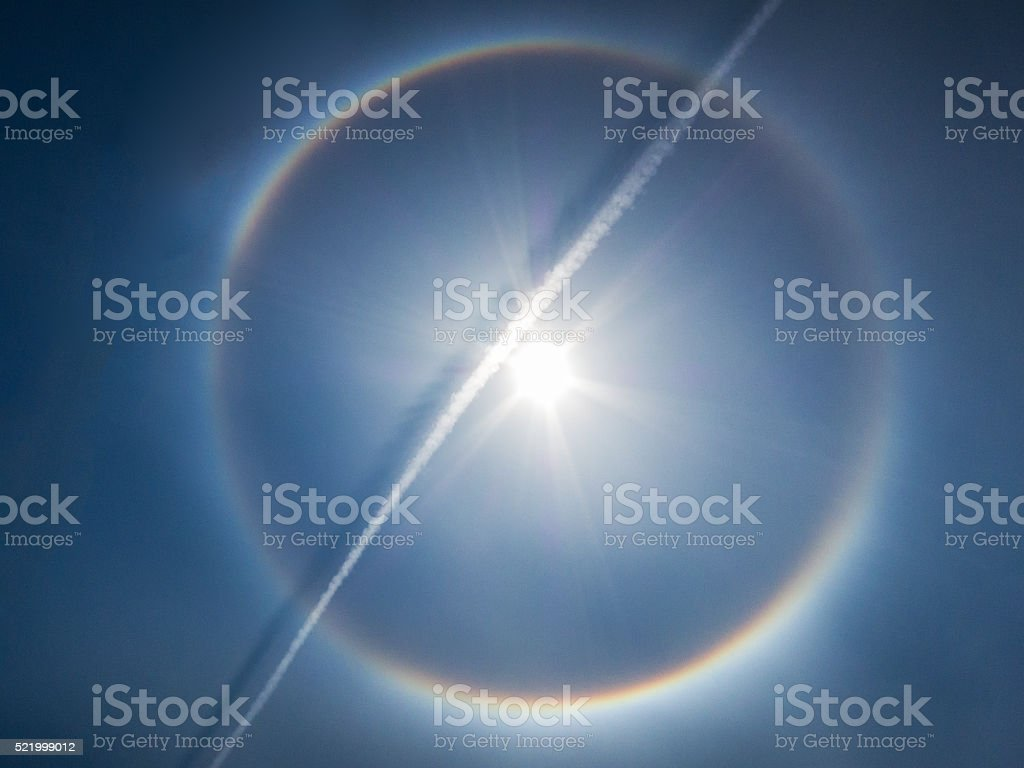 Sun Halo and contrail stock photo