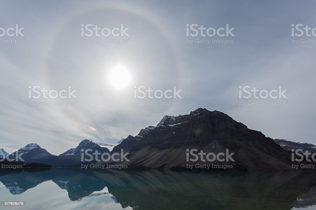 Sun Halo Over Lake Shadowed by Mountains stock photo
