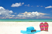 Sun hat with sunglasses and slippers on white sandy beach