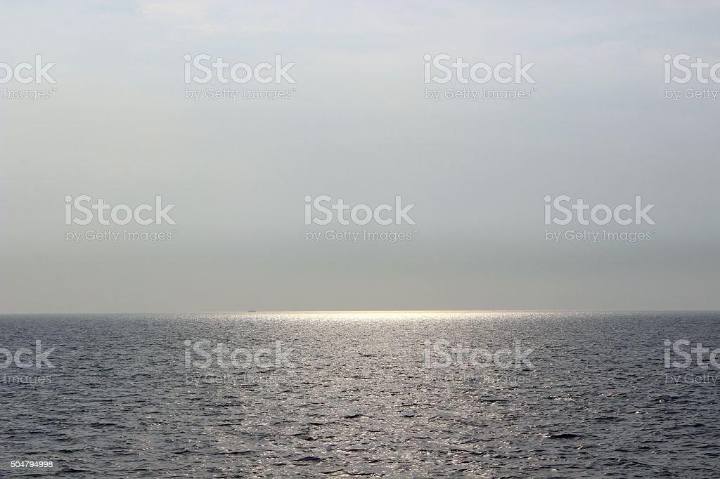 sun hiding in sea, reflection of sun stock photo
