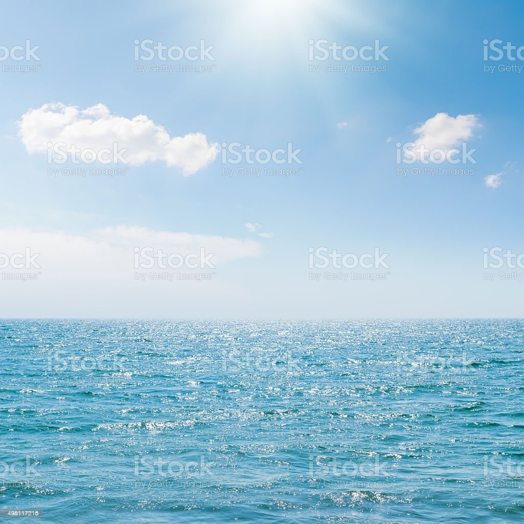 sun in blue sky over sea stock photo
