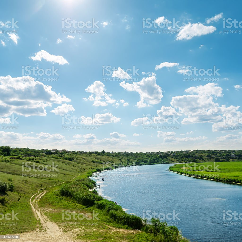 sun in blue sky with clouds over river stock photo