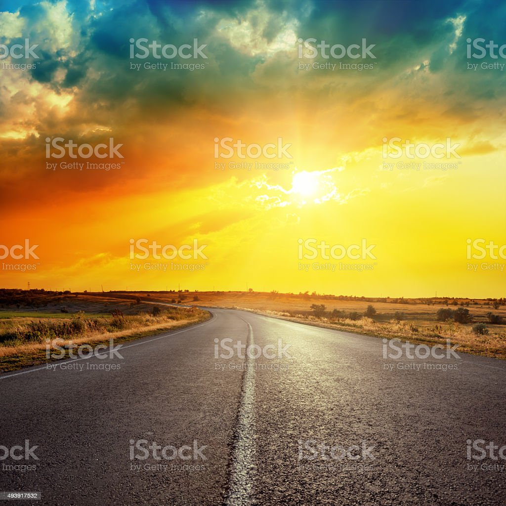 sun in clouds over road stock photo