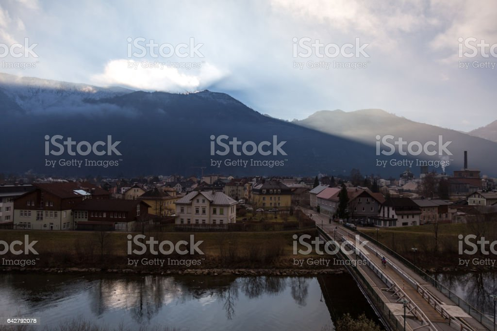 Sun is rising behind mountain above the small town stock photo