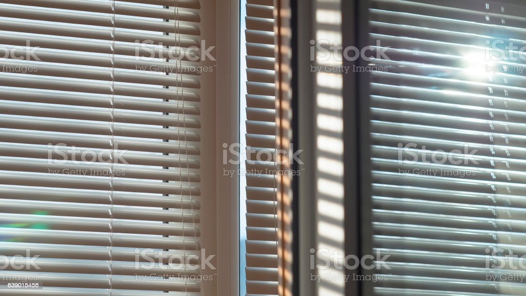 Sun is shining and glowing through the blinds stock photo