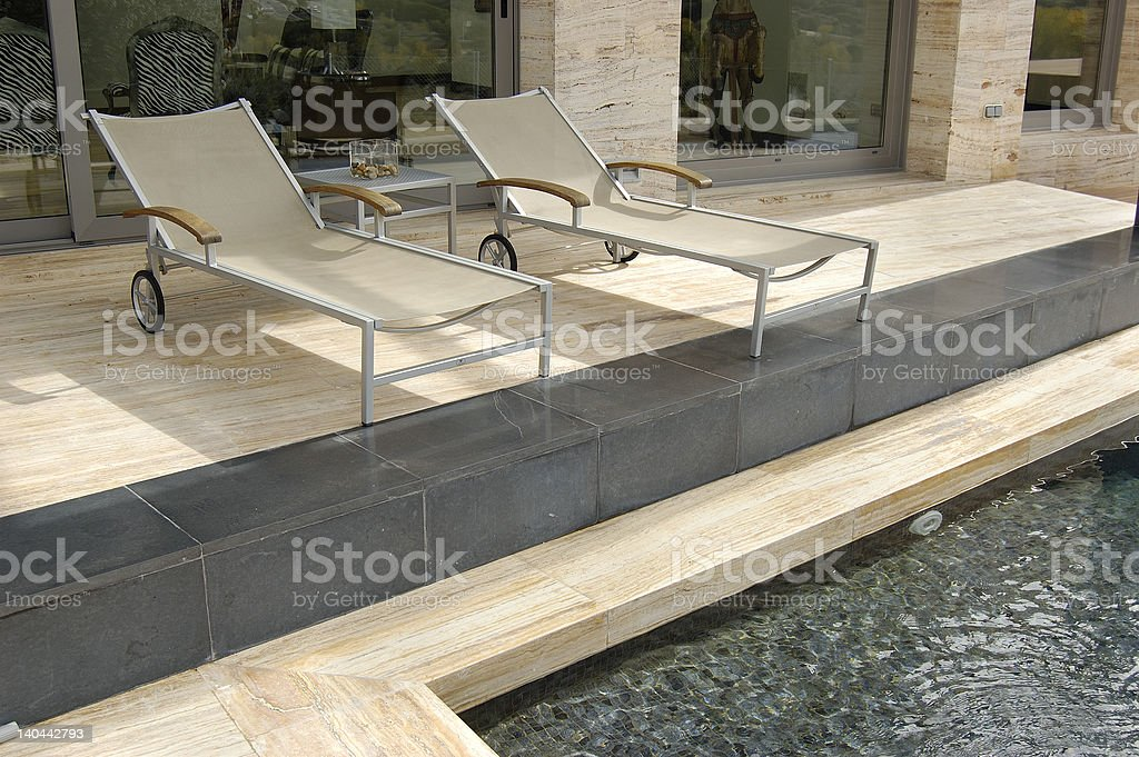 sun loungers in a swimming pool stock photo