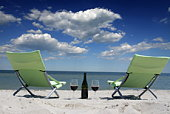 Sun loungers on beach next to bottle of red wine and glasses