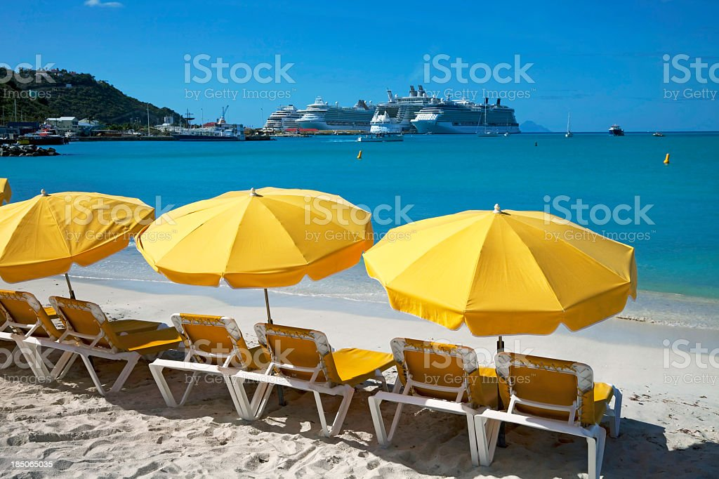 Sun loungers on beach with cruise ship in distance stock photo