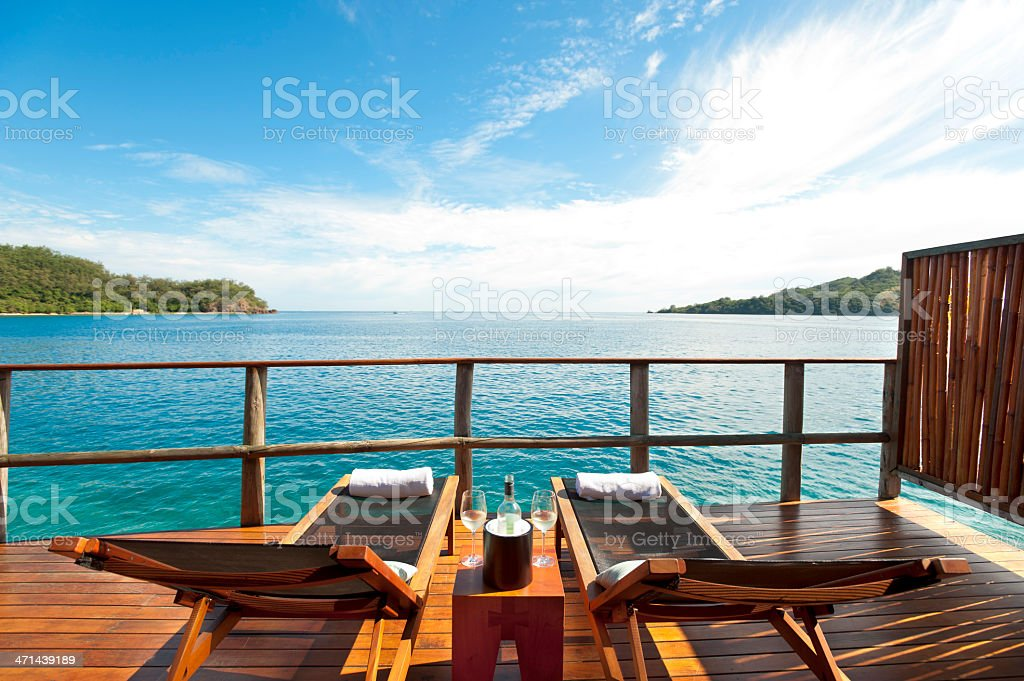 Sun lounges and wine in an over water resort stock photo