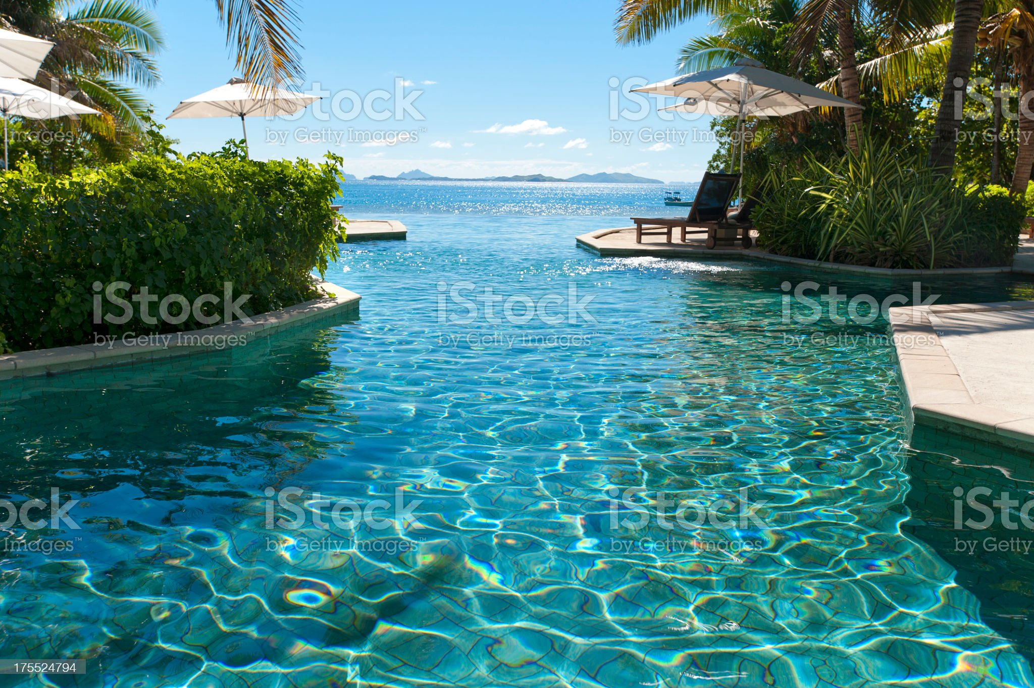 Sun lounges beside a pool with ocean royalty-free stock photo