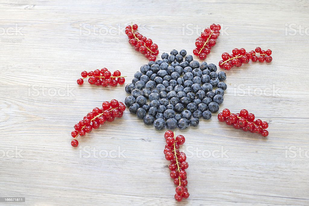 Sun made with red currant berries and blueberries royalty-free stock photo