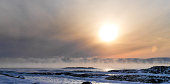 Sun over cold Foggy land covered with Snow