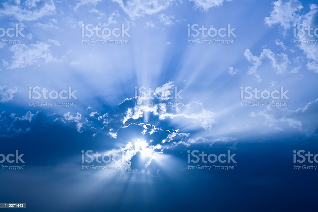 Sun radiating behind clouds in a deep blue sky royalty-free stock photo