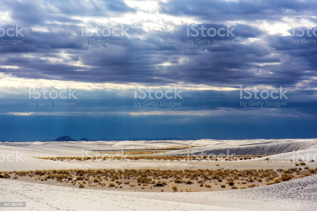 Sun rays break thought the clouds at White Sands National Monument stock photo