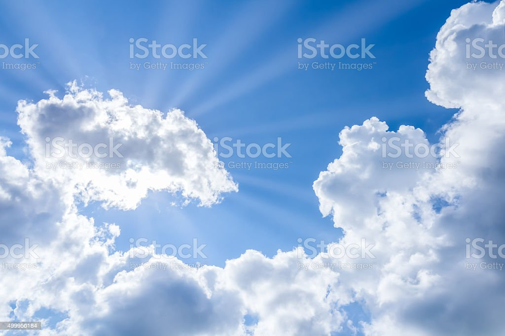 sun rays breaking through the clouds on blue sky stock photo